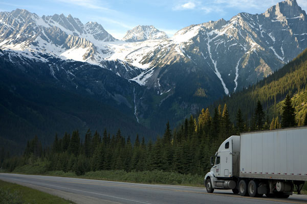 Paula's Moners long distanc moving truck heads across country on. the open road with large snow capped mountains in the distance.