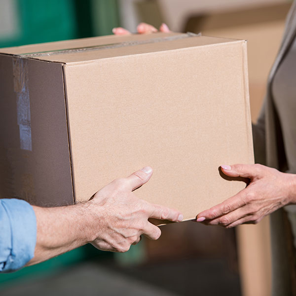 A man hands a woman a small moving box.