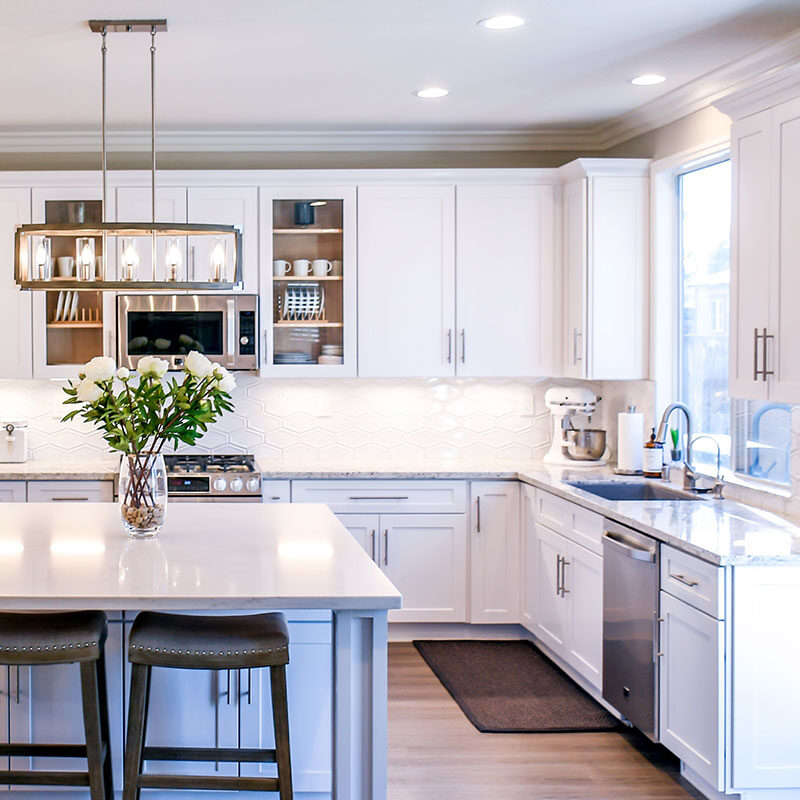 A stylish and clean kitchen organized with plates and cups in the cupboards. A vase of flowers is centered on the island counter and a kitchen aid mixer sits on the counter near the sink. Daylight shines through the window above the sink.