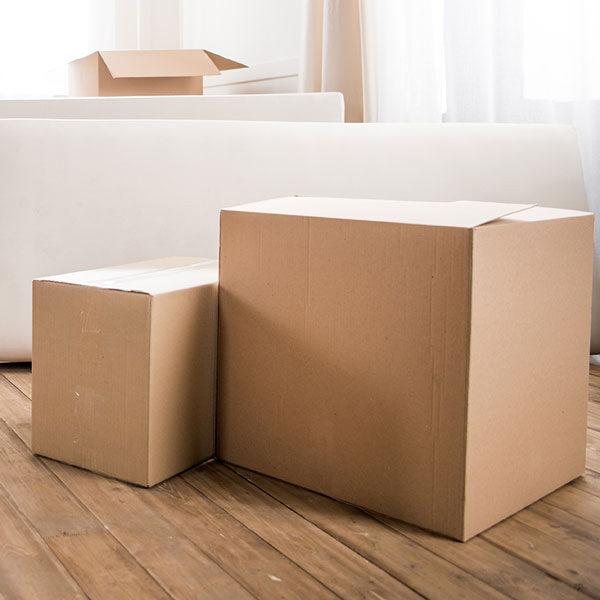 Boxes on the floor in a home. with a white sofa and a partly rolled rug. Soft, daylight shines through the white curtains.