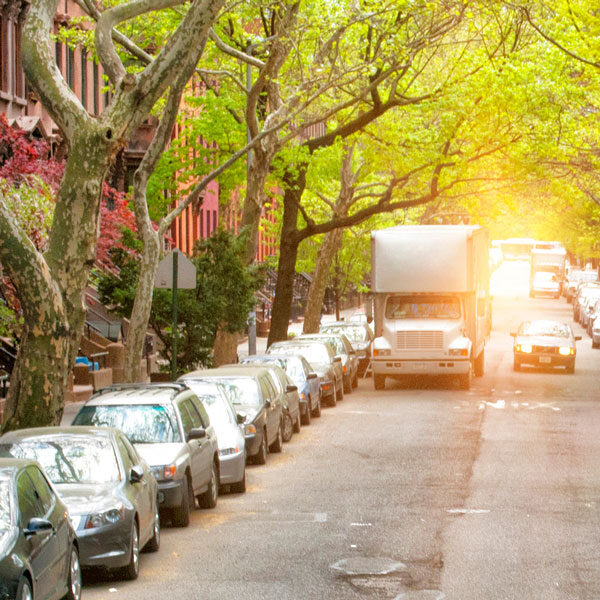 Paulas Movers Moving Truck Parked on A Brownstone lined Street In New York City.